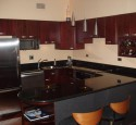 Cherry kitchen cabinets with black appliances